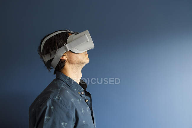 Man watching movie through virtual reality simulator by blue wall at home — Stock Photo