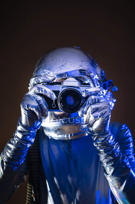 Astronauta masculino tomando fotos de la cámara contra el fondo de color - foto de stock