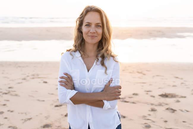 Lächelnde Frau mit verschränkten Armen am Strand — Stockfoto