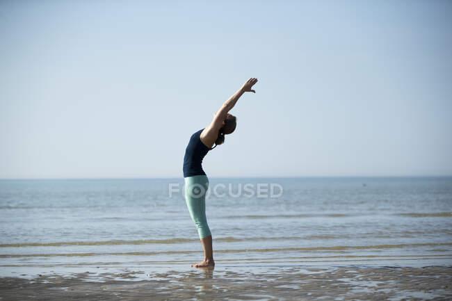 Зрелая женщина с поднятыми руками, тренирующаяся на пляже против ясного неба — стоковое фото