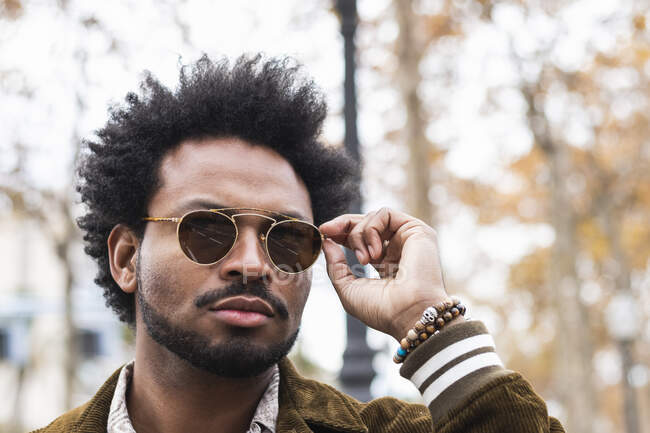 Primer plano del hombre guapo con pelo afro usando gafas de sol - foto de stock