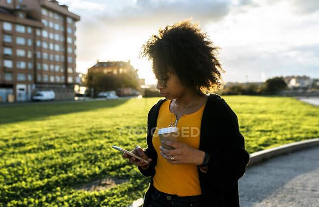 Jovem segurando café usando telefone celular enquanto caminha no caminho contra o céu — Fotografia de Stock