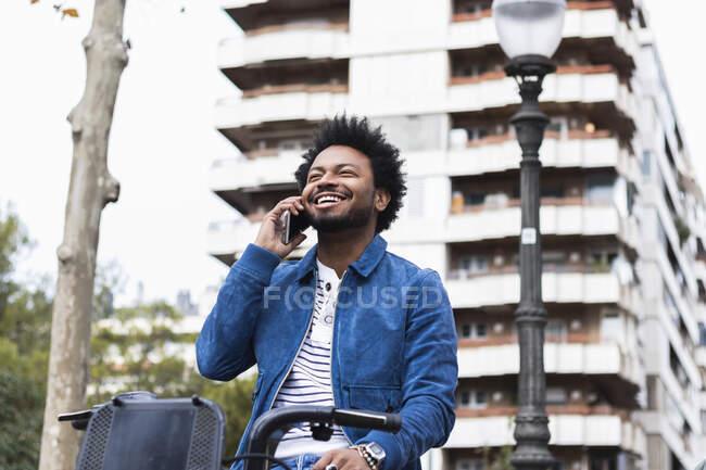 Homem alegre com cabelo afro falando por telefone celular enquanto sentado na bicicleta contra a construção — Fotografia de Stock