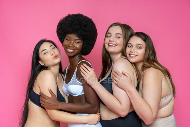 Groupe souriant de modèles féminins multi-ethniques en lingerie s'embrassant sur fond rose — Photo de stock