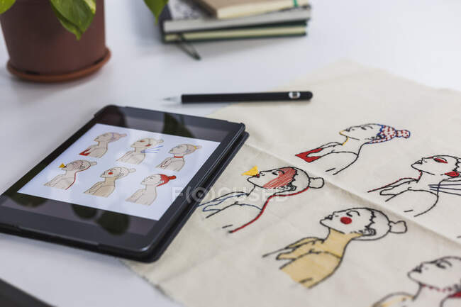 Digital tablet by textile with embroidered pattern — Stock Photo