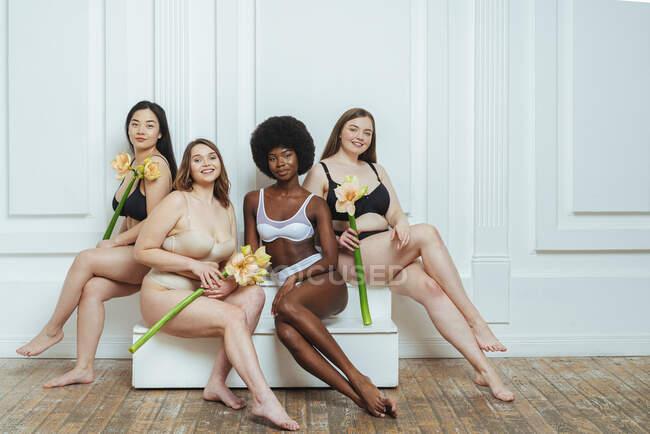 Groupe multi-ethnique de modèles féminins en lingerie tenant des fleurs tout en étant assis contre un mur blanc — Photo de stock