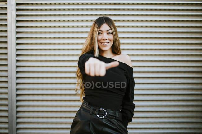Mujer joven sonriente mostrando los pulgares hacia arriba mientras está de pie contra la pared - foto de stock