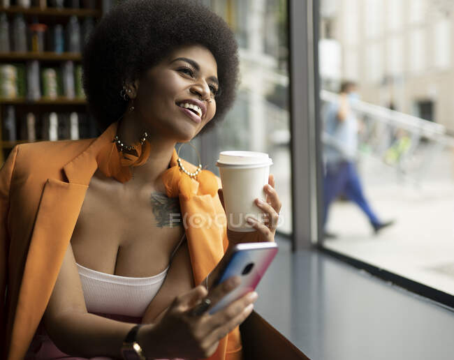 Happy woman with smart phone and coffee cup looking through window in cafe — Stock Photo