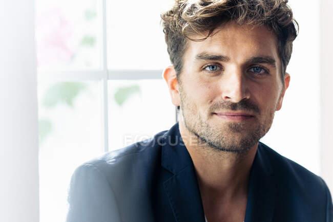 Uomo d'affari con gli occhi azzurri a fissare mentre in piedi a casa — Foto stock