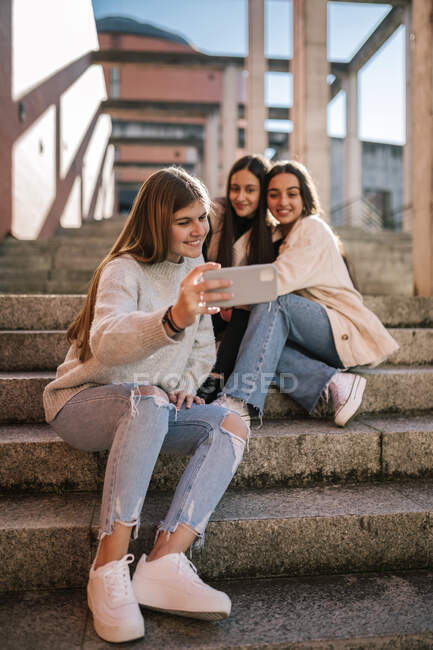 Smiling teenage girl taking selfie with friends while sitting on steps in city — Stock Photo