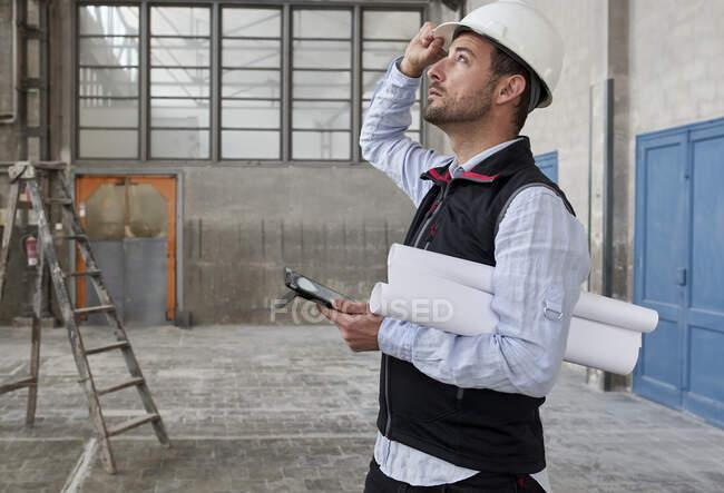 Architecte masculin avec tablette numérique et les plans levant les yeux tout en se tenant debout dans le bâtiment — Photo de stock