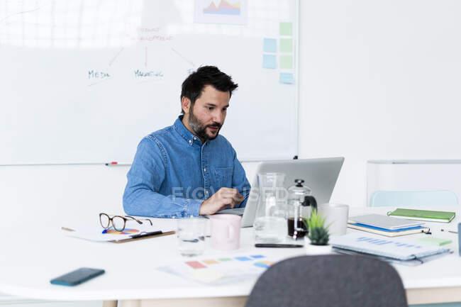 Чоловік, який користується ноутбуком в офісі. — стокове фото