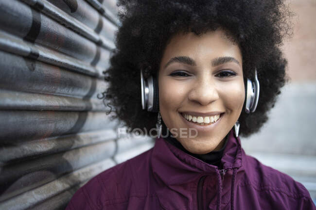 Happy young woman listening music through headphones by corrugated wall — Stock Photo