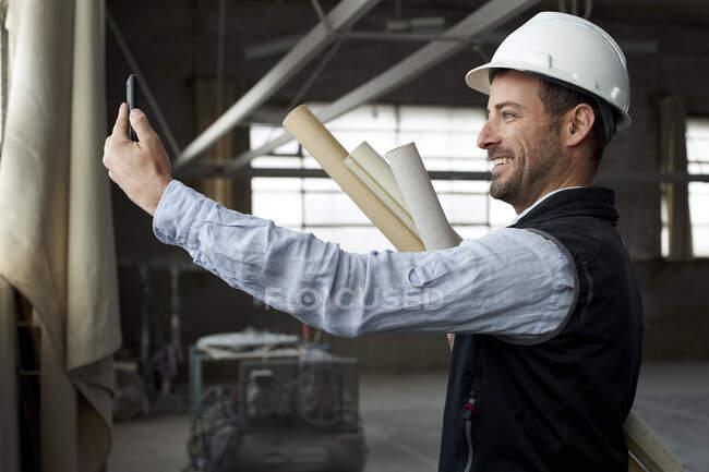 Sorrindo vídeo arquiteto masculino chamando por telefone inteligente enquanto está em pé na construção — Fotografia de Stock