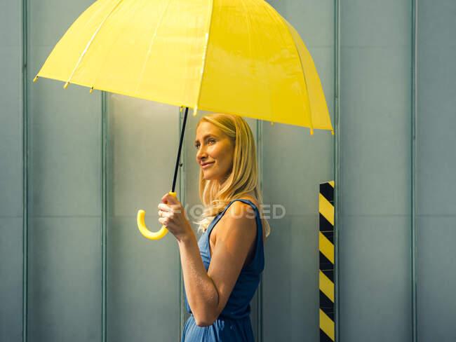 Mujer sonriente con paraguas por la pared en el día soleado — Stock Photo