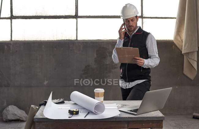Male architect discussing over smart phone while analyzing document in building — Stock Photo