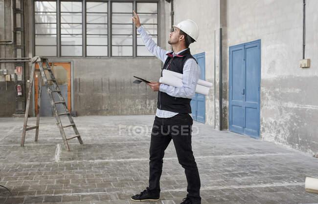 Architecte masculin avec tablette numérique pointant tout en regardant vers le haut dans la construction du bâtiment — Photo de stock