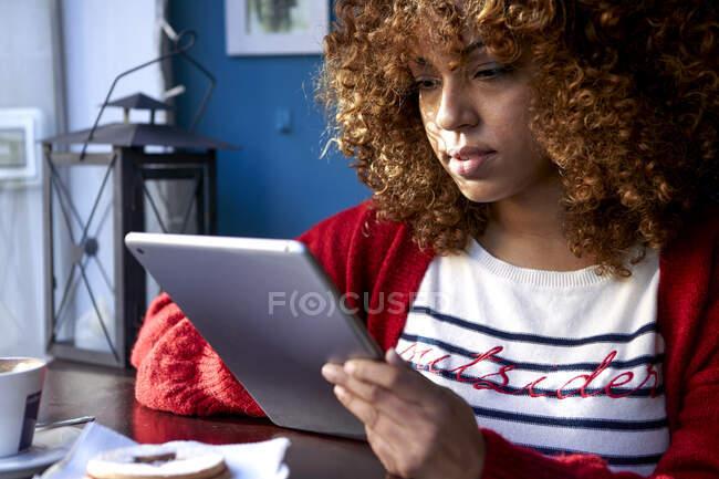Mulher usando tablet digital enquanto está sentado no café — Fotografia de Stock