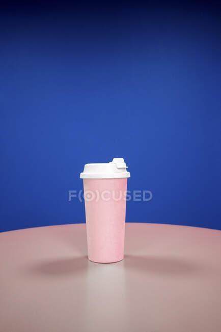 Taza de café reutilizable sobre la mesa sobre fondo azul - foto de stock