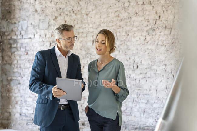 Безробітна жінка обговорює з архітектором питання під час роботи над цифровим планшетом на будівельному майданчику. — стокове фото