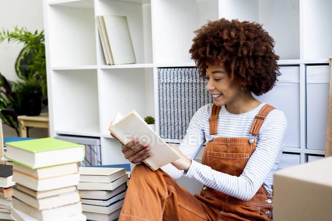 Sorrindo jovem mulher lendo livro enquanto descompactando no novo apartamento loft — Fotografia de Stock