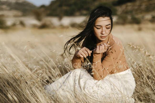 Giovane donna contemplando mentre seduto in mezzo gfrass in campo durante la giornata ventosa — Foto stock