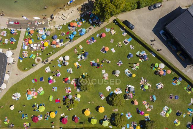 Austria, Salzburgo, Sankt Gilgen, Vista aérea de un gran grupo de personas tomando el sol en el césped verde en verano - foto de stock