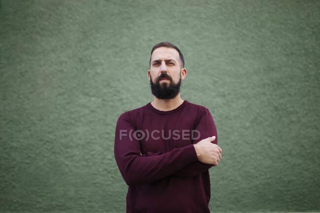 Бородатый мужчина со скрещенными руками стоит у зеленой стены — стоковое фото