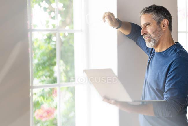 Maduro hombre de negocios con portátil mirando hacia otro lado mientras está de pie en casa - foto de stock