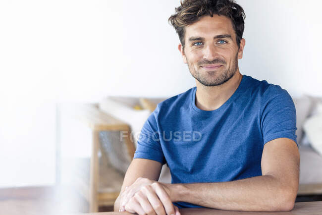 Mid adult man with blue eyes smiling while sitting at home — Stock Photo