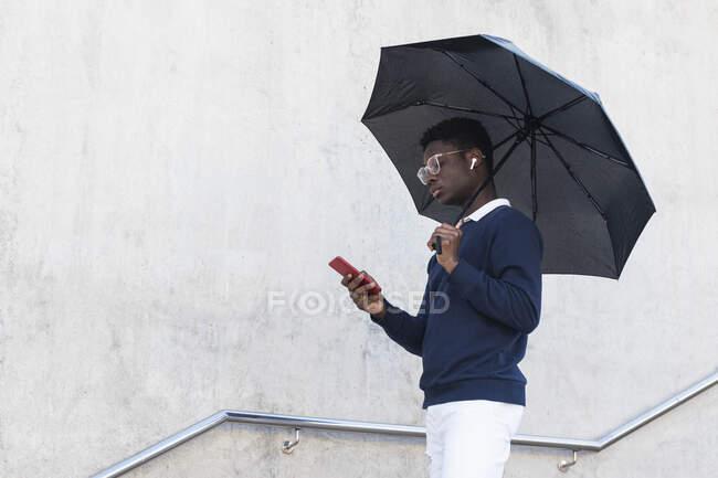 Молодий африканський чоловік з парасолевим слуханням через навушники під час користування смартфоном. — стокове фото