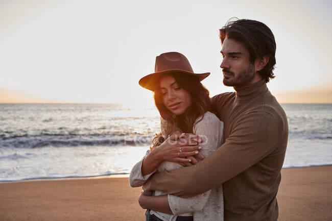 Мужчина обнимает женщину сзади, стоя на пляже — стоковое фото