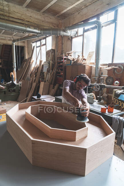 Young male carpenter making wooden furniture in workshop — Stock Photo