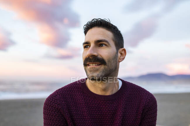 Handsome man in maroon sweater day dreaming at beach during sunrise — Stock Photo