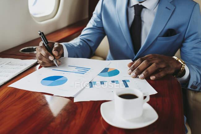 Homme d'affaires travaillant sur document en jet privé — Photo de stock