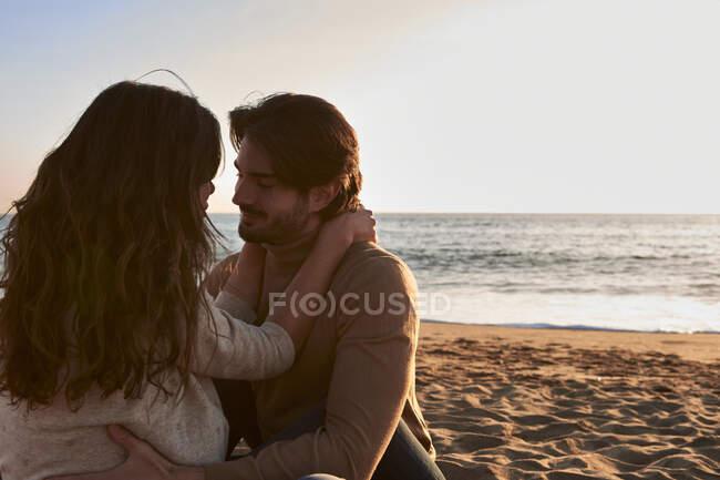 Девушка и парень, сидящие лицом к лицу на пляже — стоковое фото