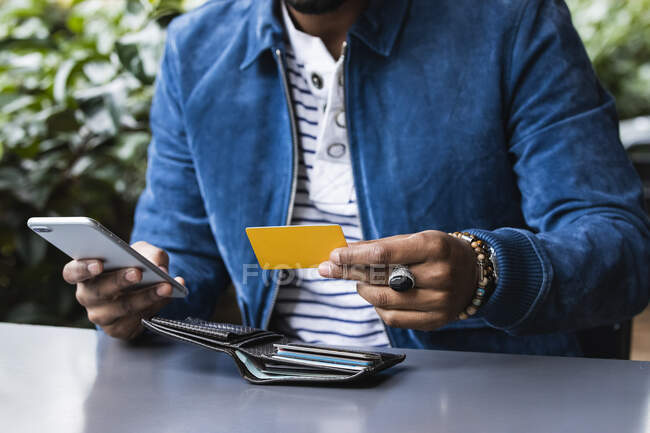 Крупный план человека с кредитной картой, совершающего мобильный платеж в кафе на тротуаре — стоковое фото