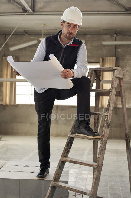 Male contractor with site plan standing in building — Stock Photo