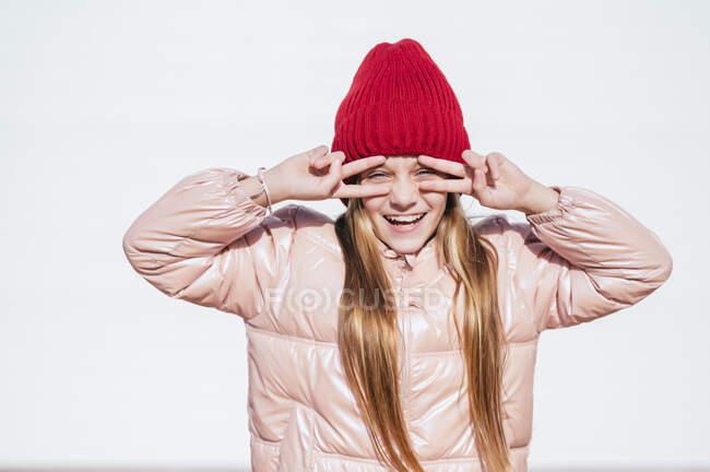 Ragazza giocosa guardando attraverso le dita mentre gesticolava segno di pace contro il muro — Foto stock