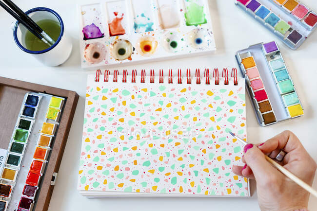 Painting pastel colors terrazzo pattern with watercolors on spiral notebook — Stock Photo