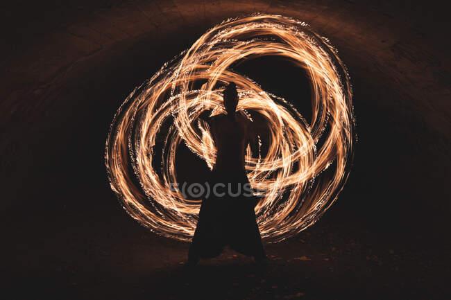 Joven realizando habilidad de anillo de fuego en túnel oscuro - foto de stock