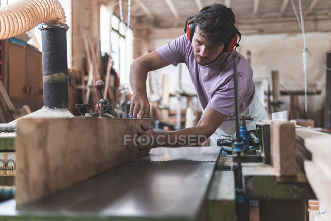 Young male craftsperson holding wooden plank on workbench while working in workshop — Stock Photo