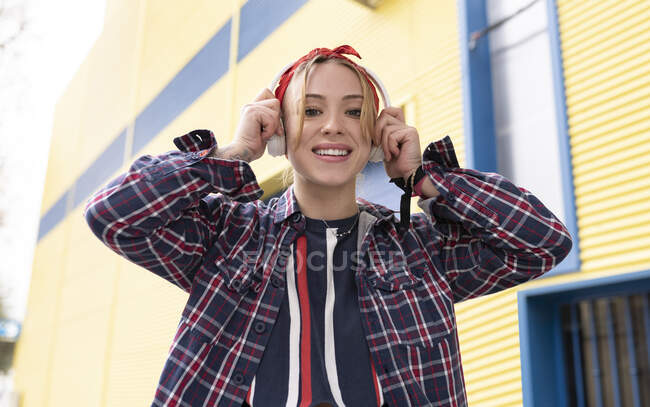 Young woman smiling while adjusting headphones standing outdoors — Stock Photo