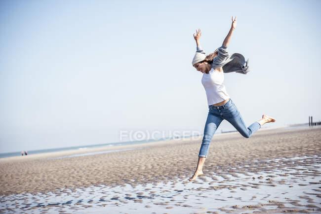 Joven alegre con los brazos levantados saltando sobre arena mojada en la playa - foto de stock