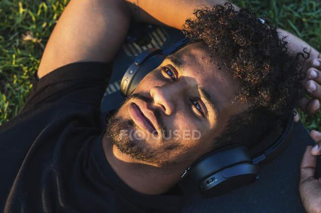 Крупный план вдумчивого человека, слушающего музыку через наушники, лежащего на скейтборде в парке — стоковое фото