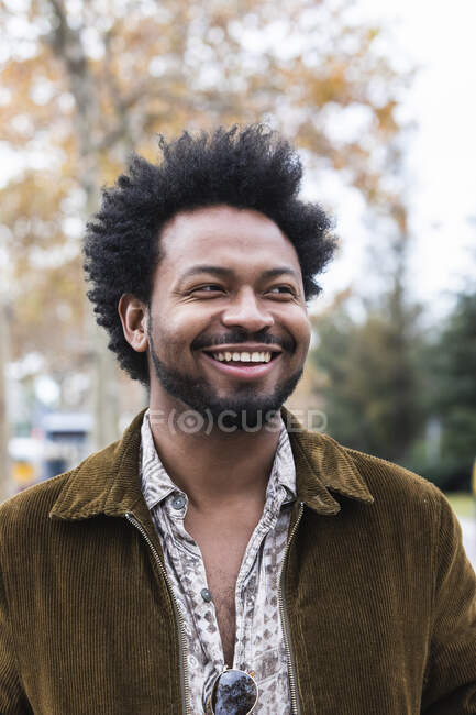 Close-up of mid adult man with afro hair laughing while looking away — Stock Photo