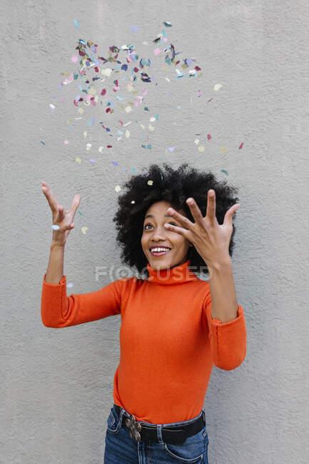 Allegro giovane donna gettando coriandoli mentre in piedi contro il muro — Foto stock
