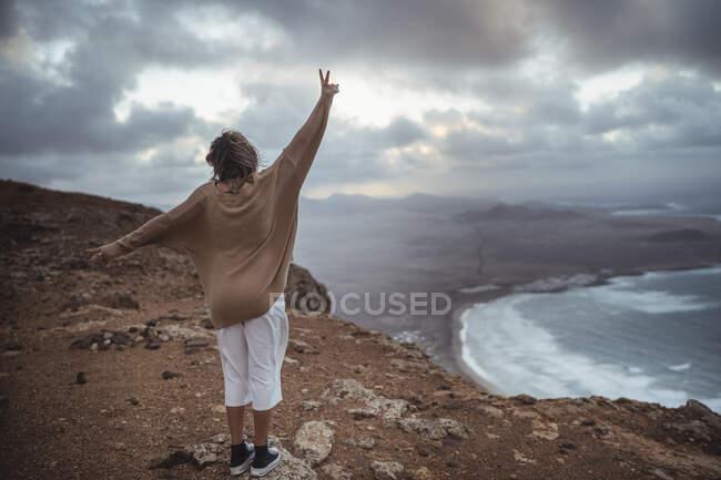 Грайлива жінка жестикулює знак миру стоячи на горі Фамара - Біч (Лансароте, Іспанія). — стокове фото