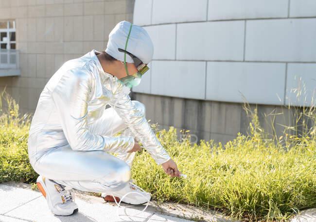Mujer joven con máscara facial de oxígeno tocando la hierba mientras se agacha al aire libre - foto de stock
