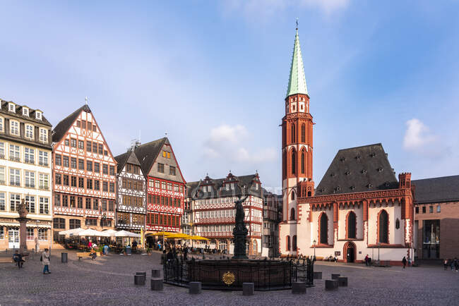 Alemania, Frankfurt, Roemerberg, Fuente de Justicia en la plaza del casco antiguo con casas de entramado de madera - foto de stock